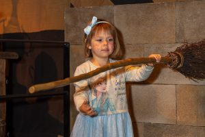 Photo of five year old girl holding a broomstick in front of her