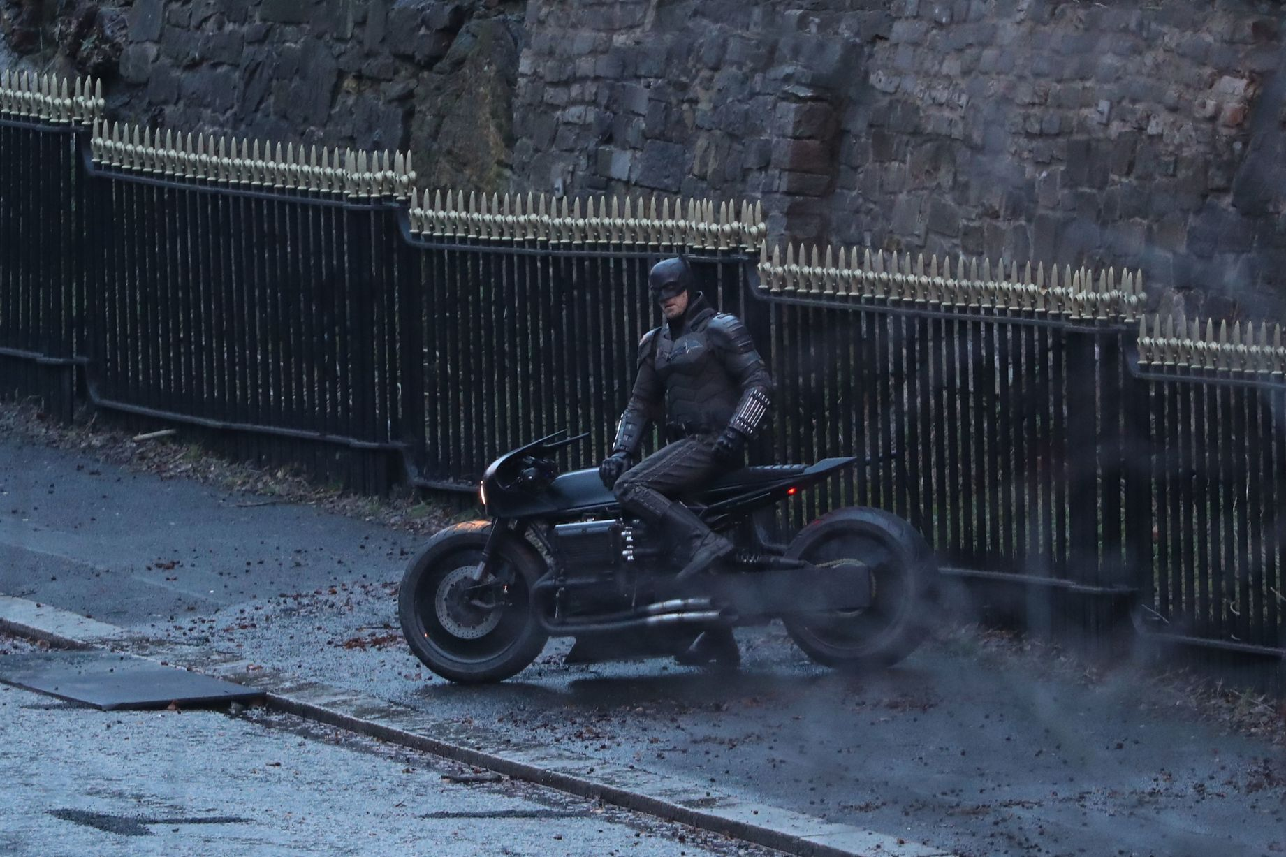 """A stuntman dressed as Batman looks cool atop the Batcycle during filming for """"The Batman""""."""