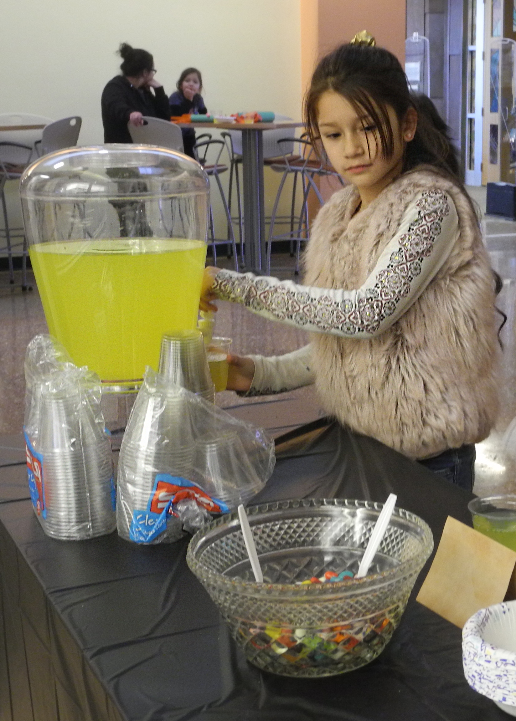 """A girl fills her cup with """"Polyjuice Potion"""" during a Harry Potter Book Night event."""