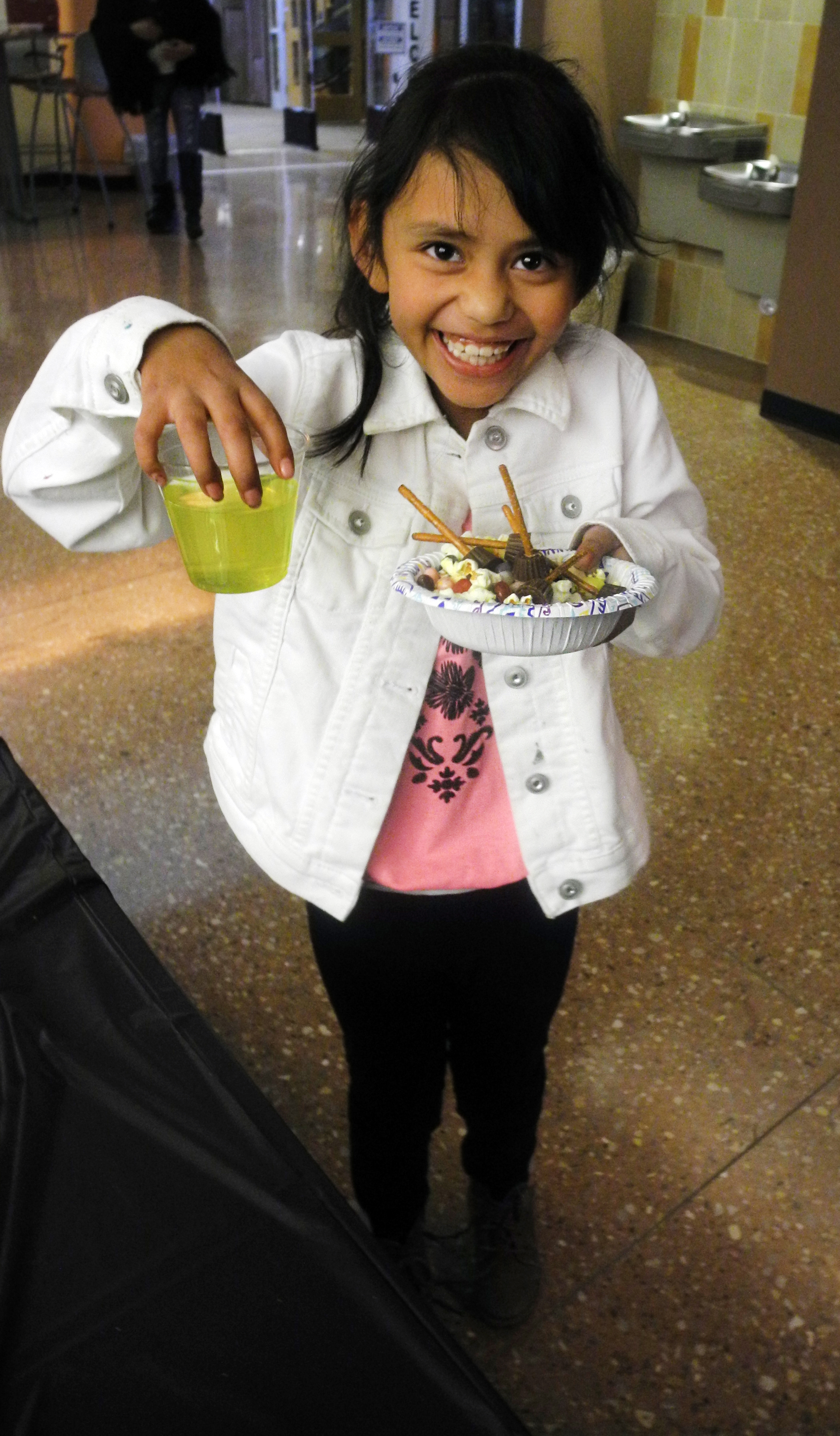 """A girl shows off her """"Polyjuice Potion"""" and """"Niffler Munch"""" at a Harry Potter Book Night event."""