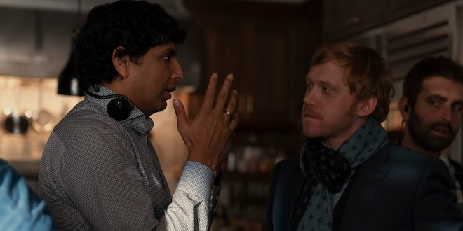 M. Night Shyamalan is directing Rupert Grint on the set of Servant. They are standing in a dark house.