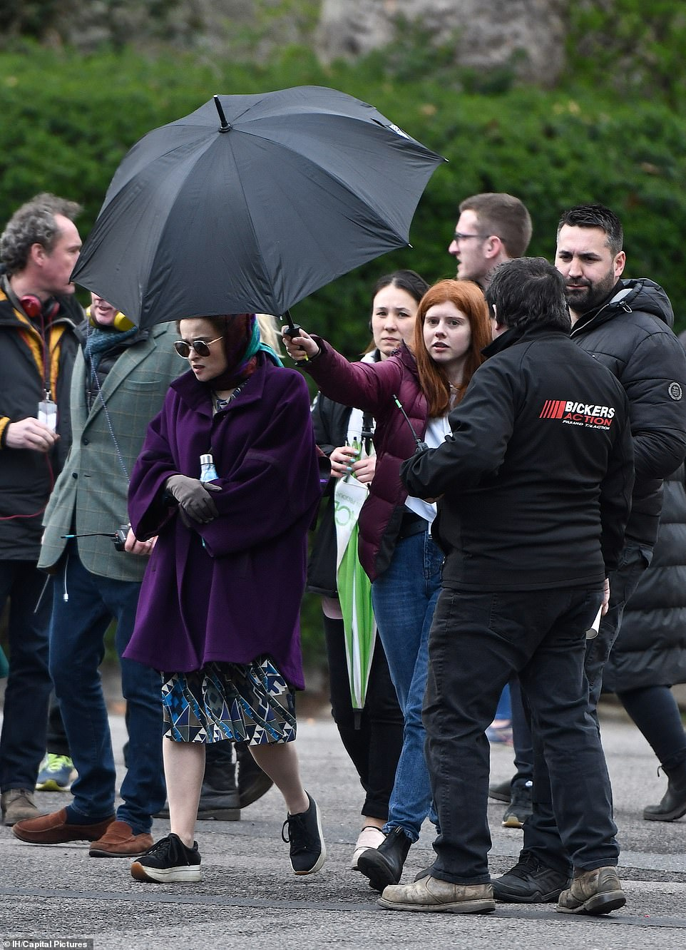 "Helena Bonham Carter is shielded with an umbrella during filming for Season 4 of ""The Crown""."