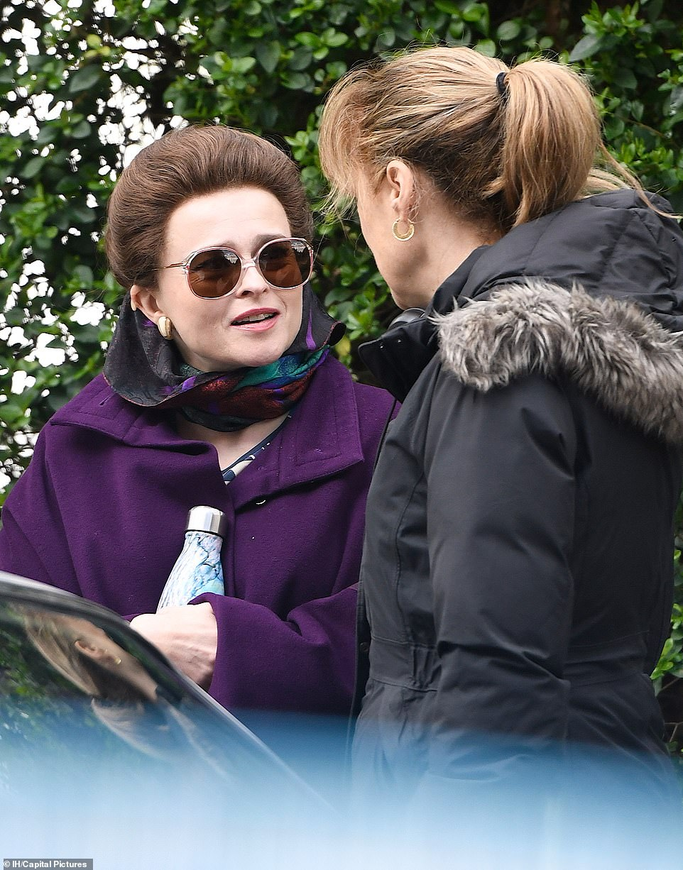 "Helena Bonham Carter talks with a crew member during filming for Season 4 of ""The Crown""."