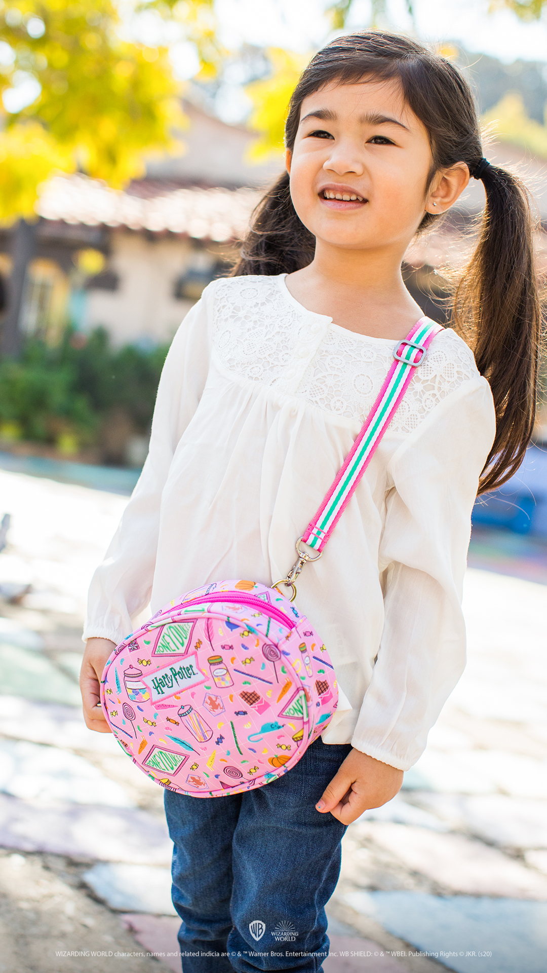 The crossbody purse features a bubblegum and peppermint strap.