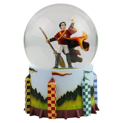 Harry Potter holds up the Golden Snitch following a triumphant Quidditch match in this snow globe from Enesco.