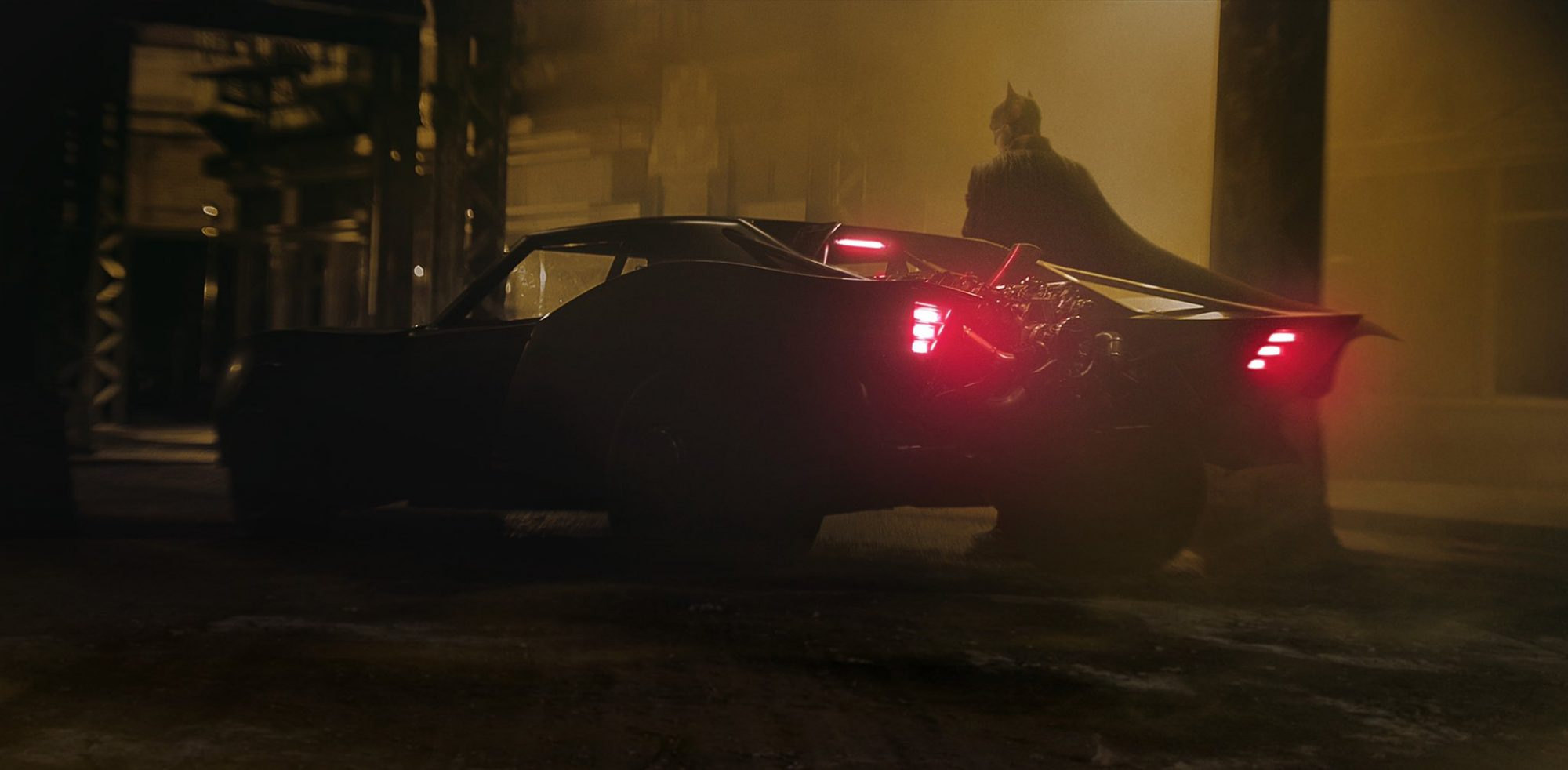 Robert Pattinson as Batman is pictured standing alongside the Batmobile.