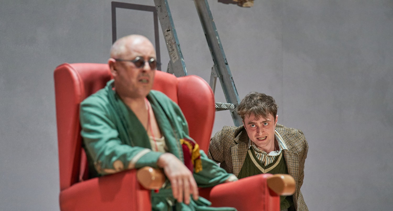 Daniel Radcliffe and Alan Cumming in Endgame on stage. Alan is in a chair as blind and disheveled Hamm while Daniel is looking at him with a mad expression.
