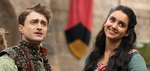Daniel Radcliffe and Geraldine Viswanathan in Miracle Workers. They are dressed in colorful medieval clothes, Dan is looking a bit confused but Geraldine is smiling.