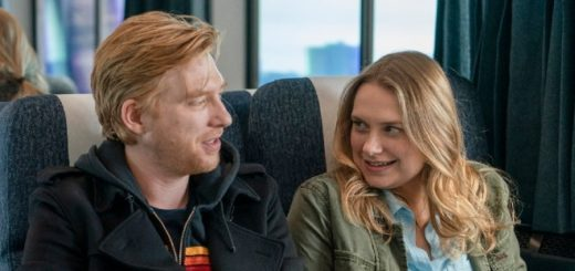 Domnhall Gleeson as Billy and Merritt Wever as Ruby sitting on a train in HBO series Run.