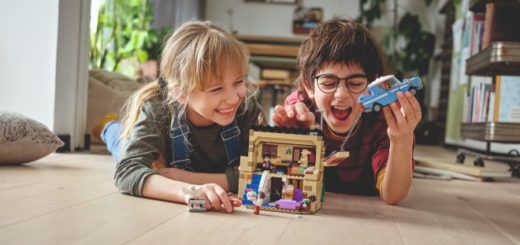 "Two children are shown playing with a LEGO ""Harry Potter"" Privet Drive set."