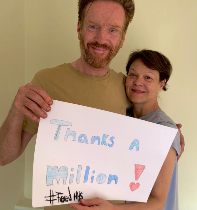 Helen McCrory and her husband, Damian Lewis, pose with a sign thanking donors everywhere after their FeedNHS initiative passed a major milestone.