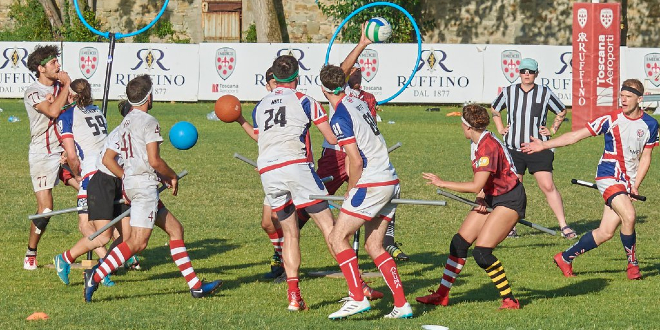 Match UK team vs. team in red-white jersey. From UK team there are male keeper, female chaser, male chaser and male beater. From red-white team there are male keeper, male chaser in the middle with quaffle, male beater with bludger, male chaser and one another player. There are also two hoops in backgroung (belongs to red-white team propably) and one referee in background.