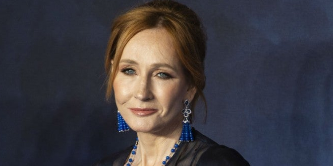 J.K. Rowling in front of blue background.