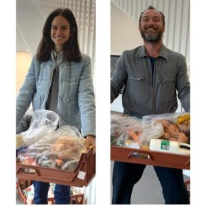 Image of katherine Waterston and Jude Law carrying food crates from the non-profit SpareHand