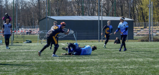 Beater Cerebro from Vienna Vanguard is beating chaser in blue jerseys who is lying on the ground. Propably another player in blue jersey is lying next to him. There is one chaser in blue jersey walking to them. On the backgroung there is one chaser who is running, one referee and someone behind camera for live-stream.
