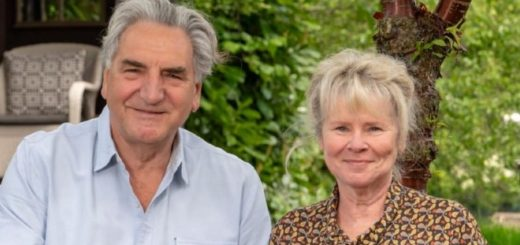 Jim Carter and Imelda Staunton are sitting in a garden and smiling at the camera.