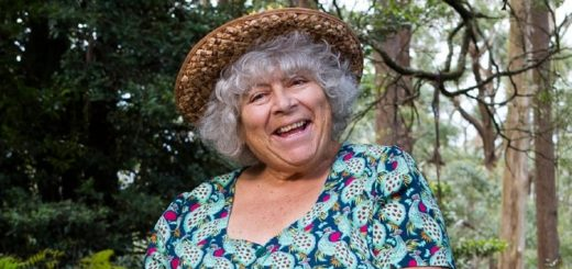 Miriam Margolyes smiles radiantly, sitting in nature in a colourful dress and a straw hat.