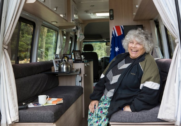 Miriam Margolyes is sitting in a nice caravan, smiling and having tea. There is an Australian flag hanging in the background.