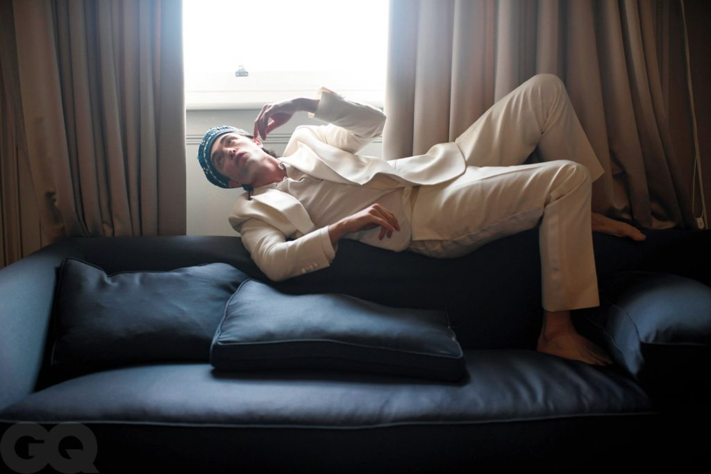 Robert Pattinson lies on top of the backrest of a black sofa by a window. He is wearing a white blazer, slacks, and T-shirt with a blue knitted hat.