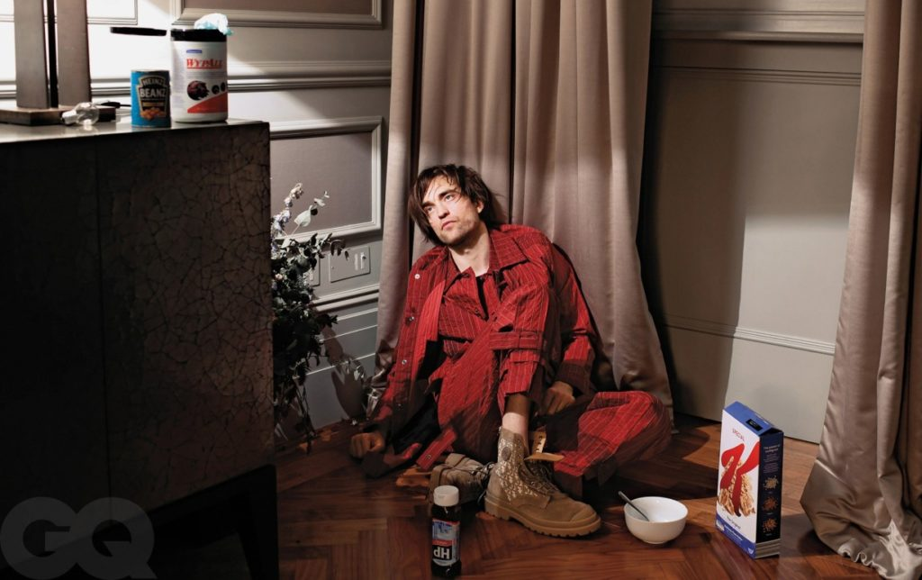 Robert Pattinson sits on his floor eating cereal and contemplating life. He is surrounded by cereal boxes and bean cans. He is stylish in an all red outfit, though.