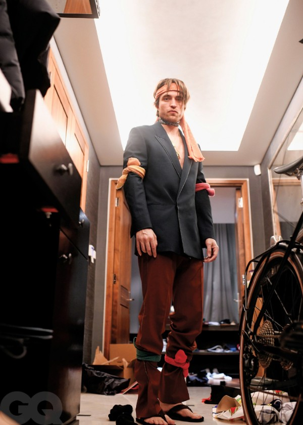 Robert Pattinson is standing in a closet. He is wearing a black blazer and brown pants, with black flip flops. He tied colourful socks around his head, arms, and legs.