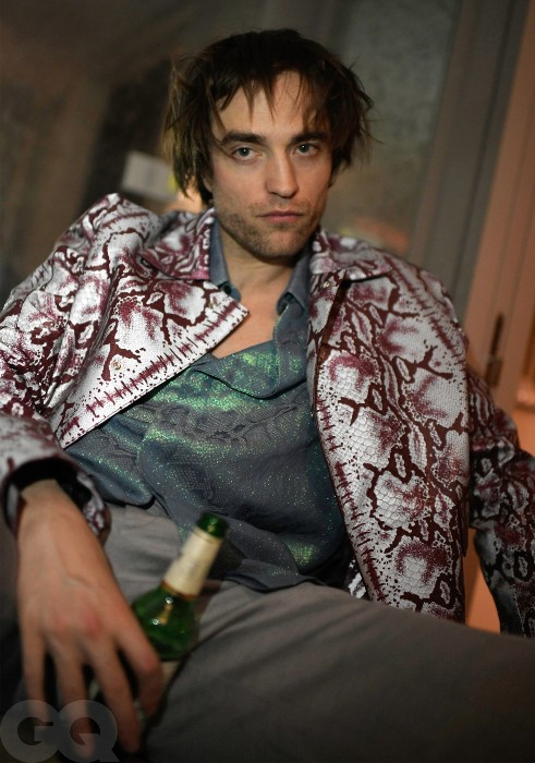 Robert Pattinson is sitting slumped on a chair. He is wearing a snakeskin patterned shirt with a similar glittery t-shirt underneath. He is holding a bottle of beer in his hand.