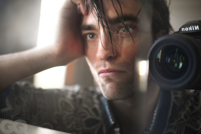 Robert Pattinson taking a selfie through the mirror up close with a camera. He looks handsome and contemplative.