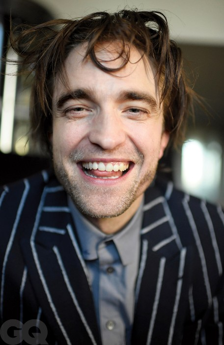Robert Pattinson takes a very smiley selfie. He is wearing a striped blazer with a grey button-up shirt. His hair is a bit chaotic but he is happy.