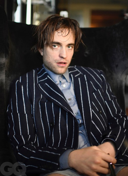 Robert Pattinson is pictured from the waist up sitting on a black couch. He is wearing a black and white striped blazer with a grey button-up and just underwear. His hair could use a comb but he is looking handsome.