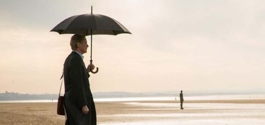 Bill Nighy stands on a beach under a black umbrella looking contemplative in Sometimes, Always, Never.