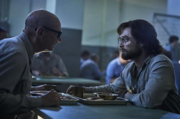 Ian Hart and Daniel Radcliffe are sitting facing each other at a prison table. They are wearing grey uniforms and seem to be having a tense conversation.