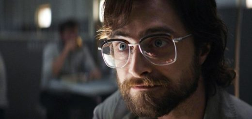 Daniel Radcliffe stares intensely off-camera as an inmate in Escape from Pretoria. He has a beard and big, old-fashioned glasses.