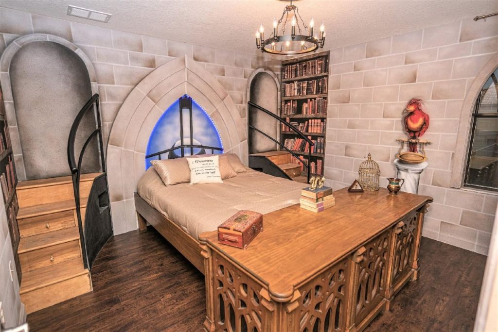 There is a bedroom with wallpaper that resembles a castle's stone walls, and painted bookshelves on each side of the bed. There is also a painting of Fawkes perched on his marble pillar. There are small steps on each side of the bed. At the foot of the bed, there is a huge desk that looks very like Dumbledore's desk.