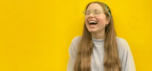 Jessie Cave laughs out loud against a bright yellow background.