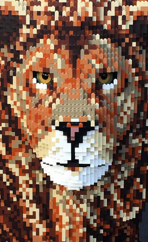 A realistic lion constructed out of plastic blocks is pictured in a promotional image for MinaLima's Art of the Block.