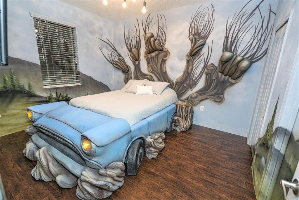 A single bed is pictured in a bedroom. The walls are painted with the landscape of the Hogwarts grounds, with a huge 3-D image of the Whomping Willow at the head of the bed. The bed is custom designed as Arthur Weasley's pale blue Ford Anglia.