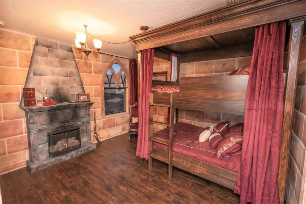A set of two bunk beds is pictured in a Gryffindor-themed bedroom. There are crimson curtains ont he bed and a fireplace.
