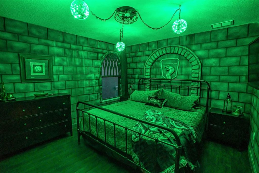 A Slytherin-themed bedroom is pictured, baking in green lights. The crest is above a king-size bed, there are Slytherin inspired knick-knkacks everywhere, including the bedding, and the walls resemble stone castles.