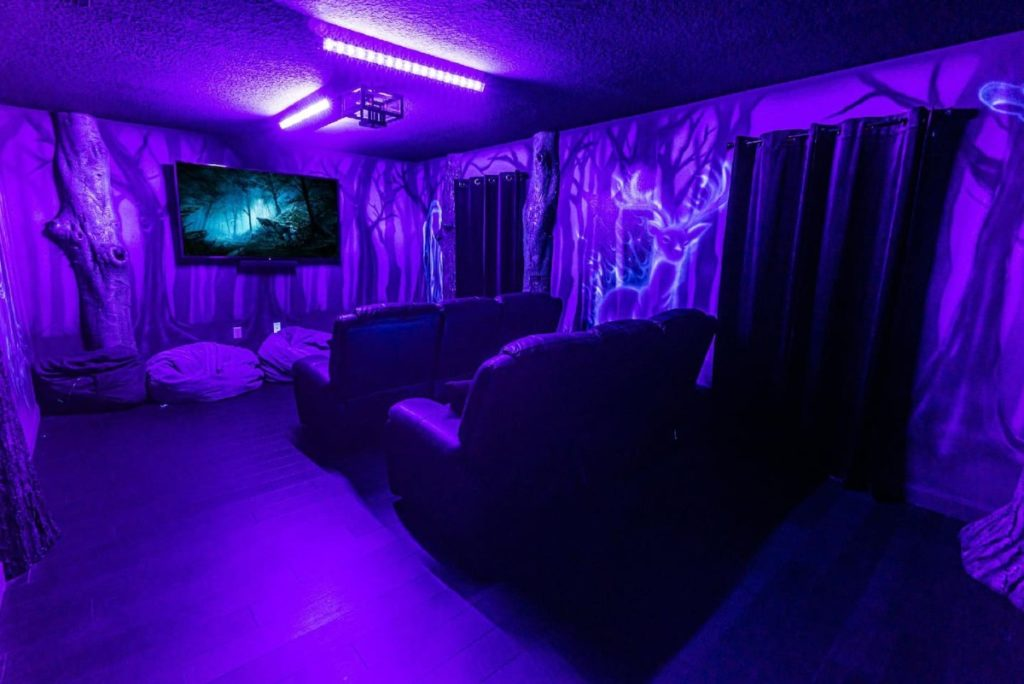 The movie room at Wizards Way has a huge flatscreen TV and bean bags as well as big couches and dark curtains.
