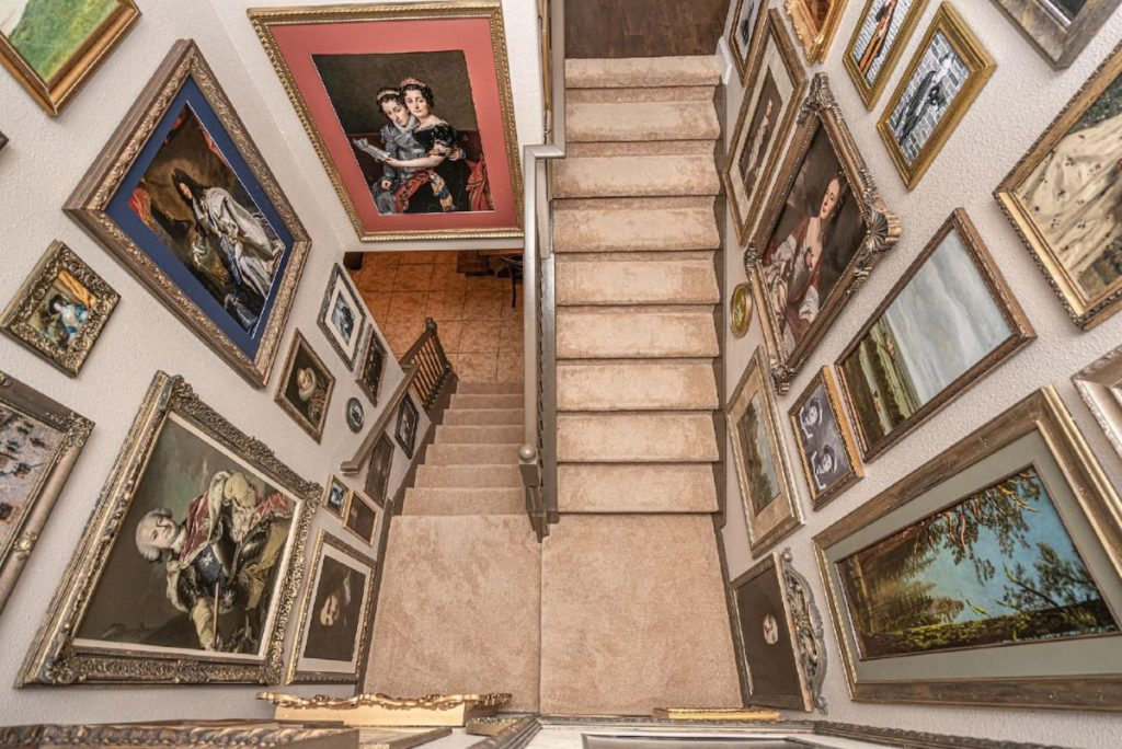 We look down on two fligths of beige stairs. All the walls are covered with paintings of monarchs and others.