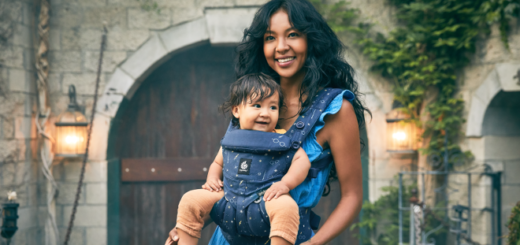 An adult and infant model the Omni 360 baby carrier from the Ergobaby Lumos Maxima Collection.