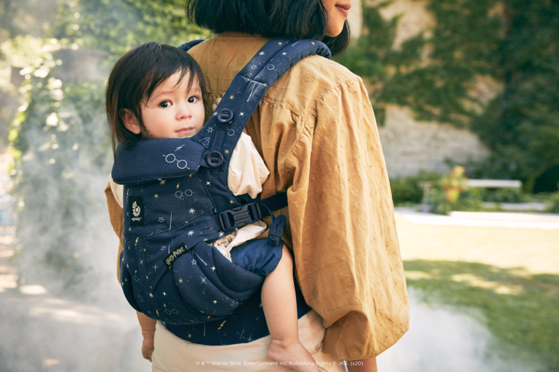An infant is pictured in the Omni 360 baby carrier from Ergobaby, in a style from the Lumos Maxima collection.
