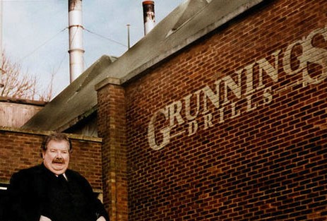 Vernon Dirsley stands next to a brick wall with the Grunnings Drills logo.