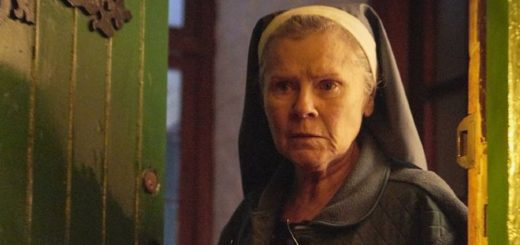 Imelda Staunton stands ominously in a dark doorway dressed as a nun.