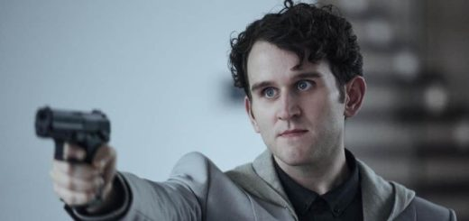 Harry Melling is dressed in a grey suit and he is pointing a gun at somebody as Merrick in The Old Guard.