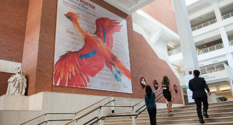 The vast open space of the British Library's steps are pictured with the phoenix cover art of A History of Magic hanging on the wall.