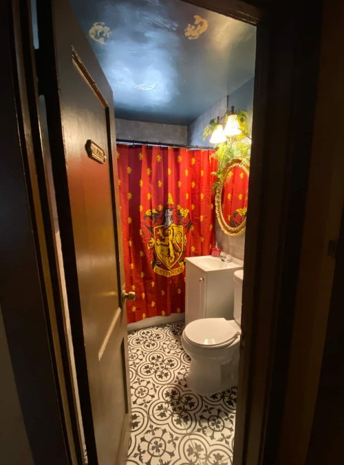 A Harry Potter themed bathroom can be seen through a door, with a cool Gryffindor shower curtain.