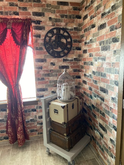 Harry Potter items, suitcases, and an owl cage are placed in the corner of a living room in an Airbnb.