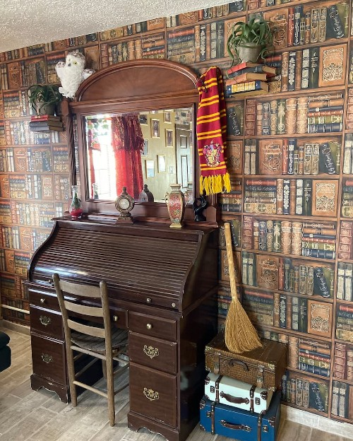 An old fashioned writing desk, a broom, suitcases, a gryffindor scarf hanging off a mirror are standing against a wall covered in a library wallpaper.