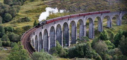 A Hogwarts Express style vintage steam train is travelling down the Glenfinnan Viaduct in the lush, green Highlands.